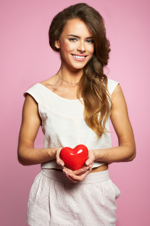 Lovely woman holding heart and smiling adorable - isolated on pink background