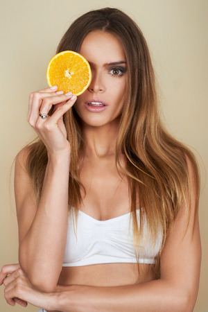 Portrait of beautiful, fresh, healthy and sensual girl over brown background with slice of orange Stock Photo