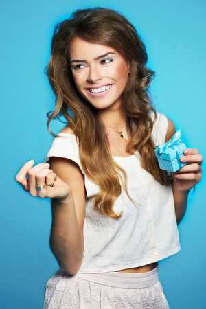 Young woman holding little present wrapped in blue, isolated on blue background