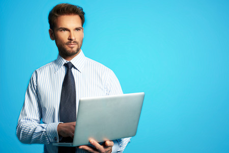 Happy business man with a laptop - isolated over a blue background