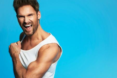 Ritratto di felice giovane uomo in casa con molto bel viso in camicia bianca su sfondo blu Archivio Fotografico - 36330371