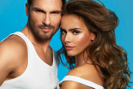 Primo piano ritratto di giovane bella coppia in amore posa in studio vestita di bianco su sfondo blu isolato Archivio Fotografico - 36330373