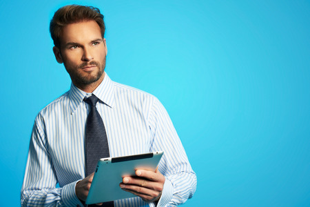 Happy young businessman in shirt using digital tablet isolated on blue background