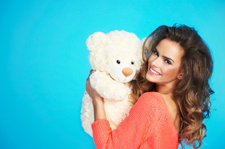 Lovely smiling young pretty woman in knitted clothes holding big soft teddy bear Stock Photo