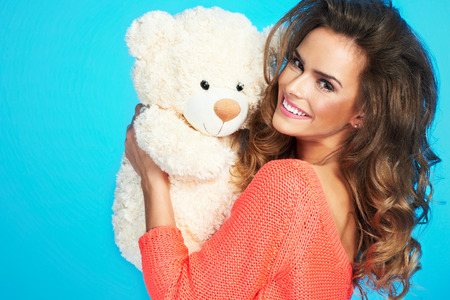 Close up portrait of a beautiful woman with teddy bear, isolated over a blue background
