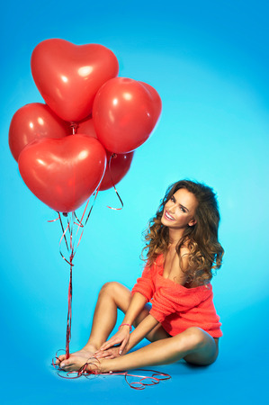 Young happy girl in love with red heart shaped balloons, sitting on a floor and smiling adorable over blue background