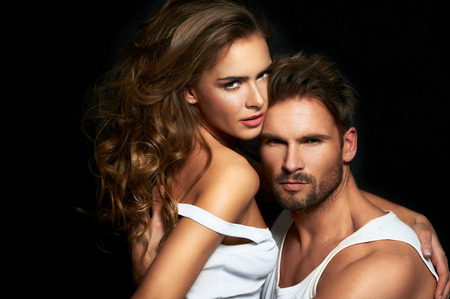 passion: Beautiful couple in white posing over a black fashion background