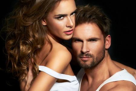 Sexy mujer y el hombre en las relaciones de intimidad, pareja de moda posando en el estudio