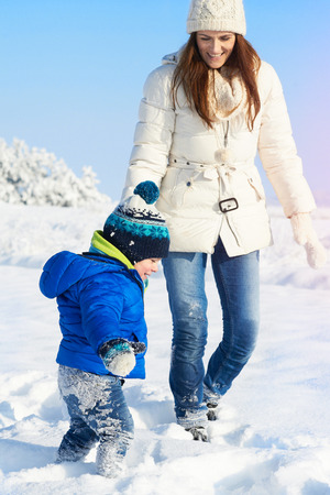 Happy young mother and child having fun outdoors in winter snoy and sunny day