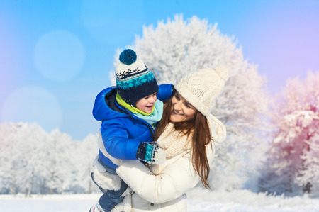 Mother and son enjoying beautiful winter day outdoors, lovely winter time Stock Photo