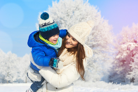 Young happy mother and her little toddler baby boy enjoying walk in beautiful snowy winter sunny day