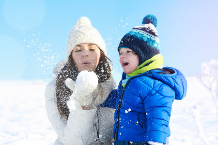 Lovely family having fun outdoor - snowy woodland