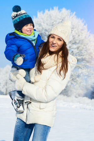 Happy smiling family in snowy day - winter portrait of mother and baby boy