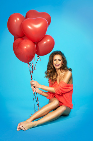 Stylish, smiling, beautiful woman with balloons in hands over blue background Stock Photo