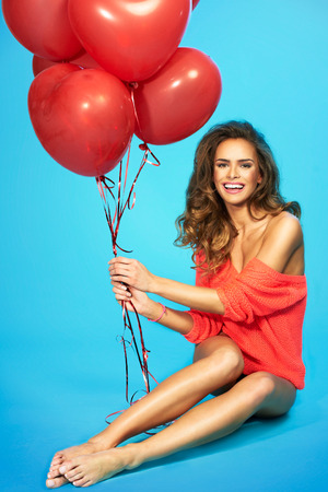 Happy pretty woman holding bunch of red air balloons at the studio Stock Photo