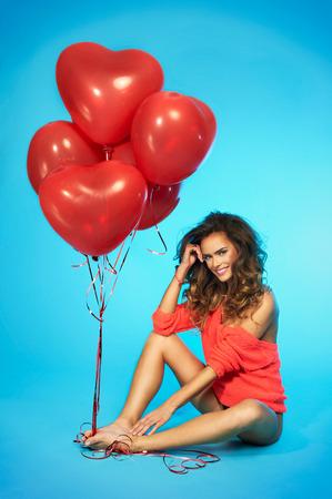 Elegante, sorridente, bella donna con palloncini in mano su sfondo blu Archivio Fotografico - 36405525