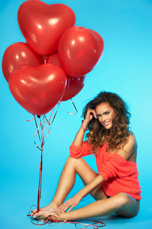 Young beautiful dark hair woman holding red balloons on isolated blue background