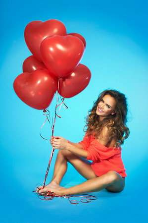 Beautiful woman with balloons over blue background