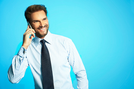 Happy young businessman in shirt using digital phone isolated on blue background Stock Photo