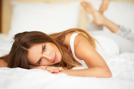 Happy delicate woman lying on bed with crossed legs looking into camera in bedroom Stock Photo