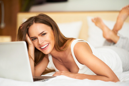 Beautiful young woman relaxing on her bed in white casual shirt using laptop Stock Photo