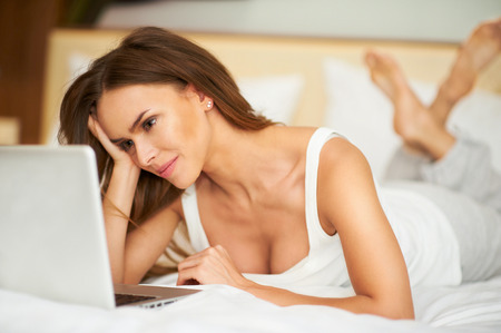 Portrait beautiful smiling young brunette woman laying in bed relaxing using laptop computer Stock Photo