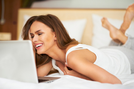 Smiling beautiful woman lying down on bed in front of laptop with legs raised slightly
