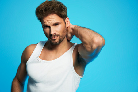 Good looking young man in white undershirt against blue background