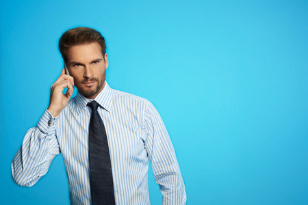 Handsome businessman in shirt and tie speaking on the phone over blue isolated background