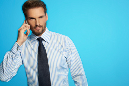 Businessman communicating standing on the phone - isolated on blue background Stock Photo