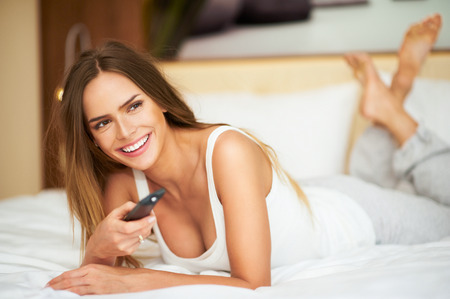 20 24: Young delicate beautiful woman laying on a bed with remote control, smiling and watching tv