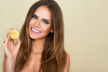 Close up portrait of attractive caucasian smiling brunette woman holdin lemon and looking at camera isolated on brown studio shot Stock Photo