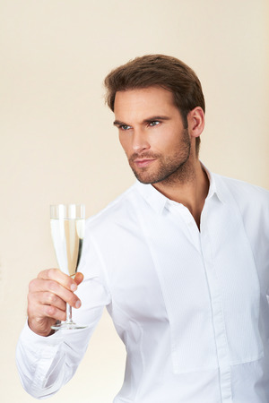 Young businessman holding glass of champagne