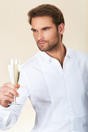 Handsome man in white shirt celebrating with a glass of champagne