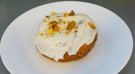 An up close view of A Pistachio Covered Cream Cheese Iced Cake Doughnut served on a white plate Stock Photo
