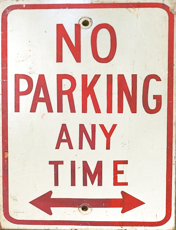 A close up of a no parking anytime sign with arrows. Foto de archivo