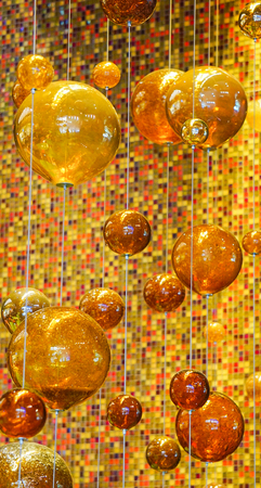Las Vegas, Nevada: May 11, 2018: Orange and Yellow Glass balls hung with wire from the ceiling at The Aria Resort and Casino Lobby