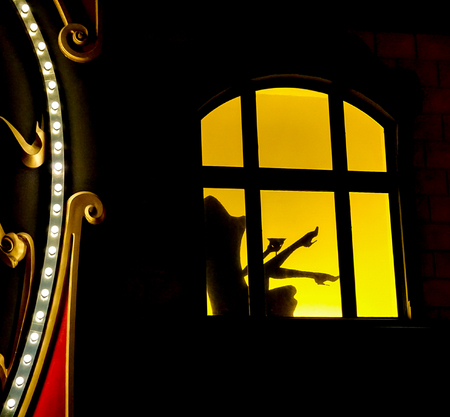 Las Vegas, Nevada: May 11, 2018:  A window lit up with shadow of a person drinking sitting in a chair with legs and high heels in the air inside  of the Paris Hotel and Casino