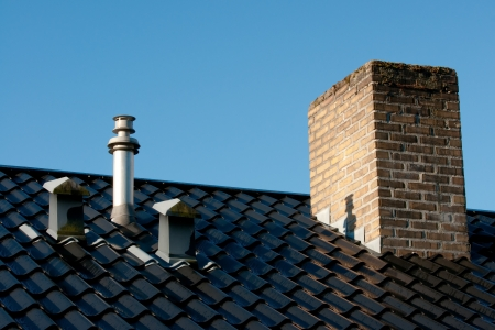 Steel roof with ventilation pipes, flue terminal from natural gas boiler and old chimney in early morning light There is still dew on the roof