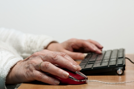 Older womans hands typing and using mouse photo