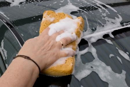 Womans mano con esponja de lavado de coches photo