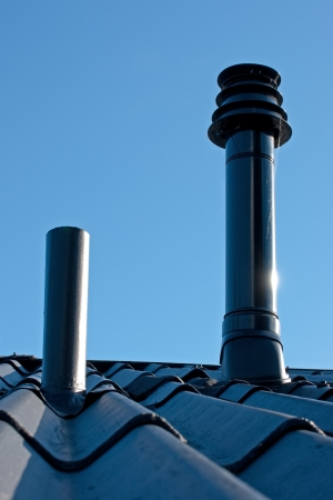 Eternit roof with ventilation pipe and flue terminal from natural gas boiler photo
