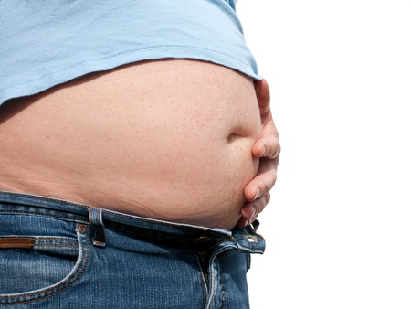 Man with fat beer belly, dressed in jeans and t-shirt, holding his hand on the belly as if he is in pain photo