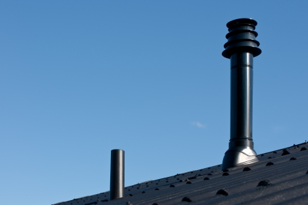 Roof with ventilation pipe and flue terminal from natural gas boiler