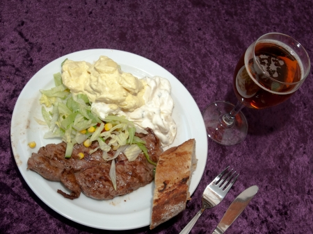 velours: Grilled steak served with green salad, potato salad and bread, with a glass of beer Stock Photo