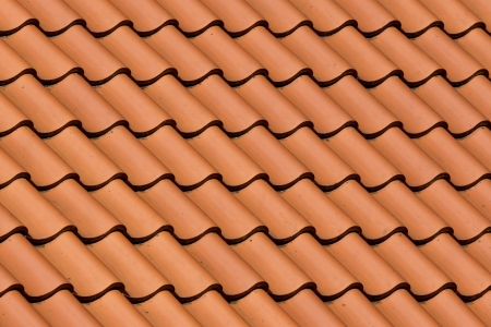 Close up of red roof tiles in horizontal and  diagonal pattern