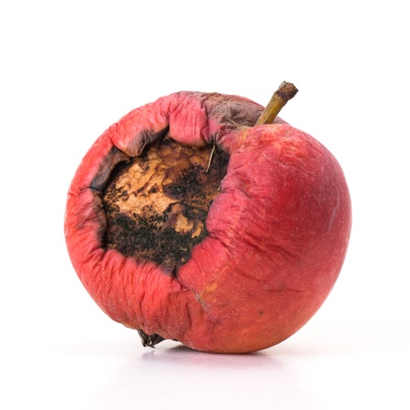 Rotten red apple with large hole on white background