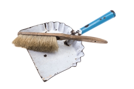 Old dustpan with a broom laying across it on white  photo