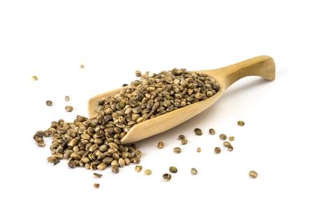 marihuana: Cuchara de madera con semillas de c��amo en el fondo blanco Foto de archivo