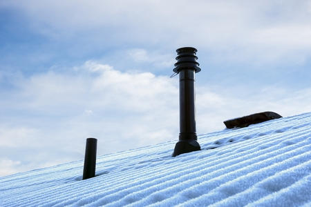 flue season: Snow covered roof with ventilation pipe and flue terminal from natural gas boiler